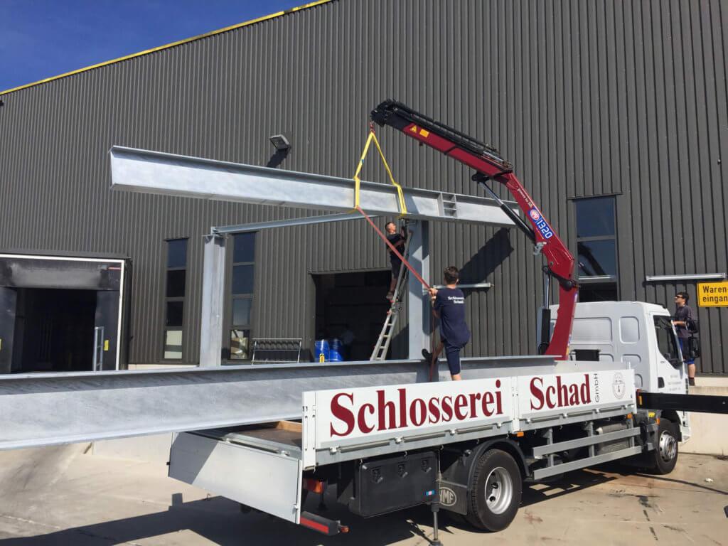Montage eines freitragenden Vordaches mit einer Länge von ca. 10m. Der oben gezeigte Stahlträger wird hier auf Position gehoben.
