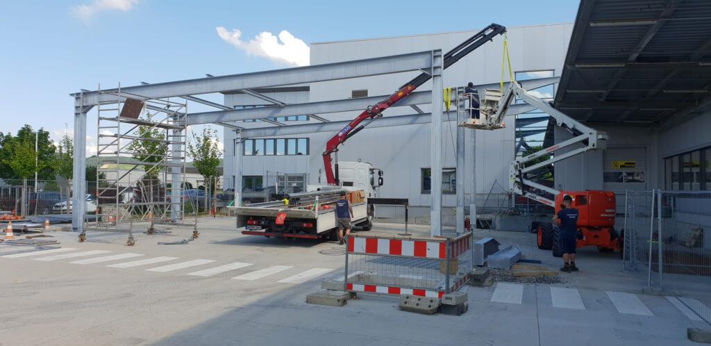 Hofüberdachung aus Stahl: Stahlbau wird montiert mit Kran und Hebebühne