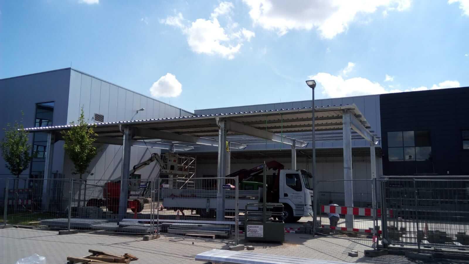 Hofüberdachung aus Stahl: Dachbleche sind zur Hälfte montiert